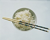 Cooked White Rice in Bowl with Chop Sticks