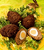 Mince frikadellas stuffed with eggs on endive salad