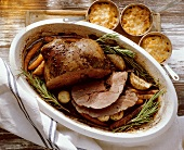 Leg of venison with vegetables in roasting tin, pumpkin gratin