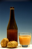 Potato juice in glass and bottle and two potatoes