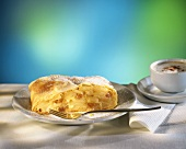 A piece of apple strudel on plate and cup of cappuccino