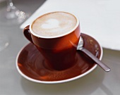 Capuccino in Brown Cup with Saucer and Spoon