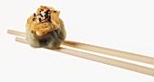 Chopsticks holding dim sum, filled with black cumin & sesame