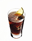 Bacardi and coke with ice cubes and lemon wedge in glass