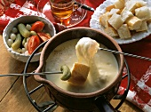 Skewers with bread & mixed pickles above cheese fondue