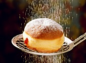 A fritter on scoop being sprinkled with icing sugar