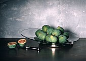 Whole Fresh Figs on a Glass Plate and a Halved Fig; Knife