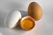Weißes & braunes Ei & ein aufgeschlagenes halbes Ei