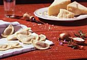 Selbstgemachte Ravioli auf Küchentuch, Parmesan & Schalotten