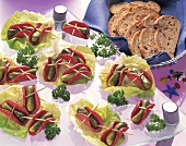 Salami & cucumber snacks on lettuce leaves & bread in basket
