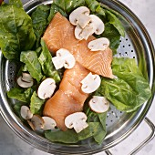Steaming: salmon, spinach & mushrooms in steamer tray in pan
