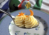 Two rosettes of creamy mashed potato on spoon