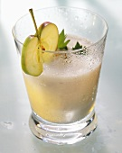 Apple & celery juice in glass, garnished with apple slice