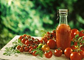 A bottle of tomato juice & fresh tomatoes on wooden table
