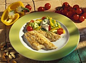 Plaice fillets with almond crust & mixed salad on plate