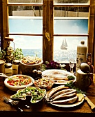Several cold matje & herring dishes in front of kitchen window