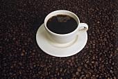 Kaffee in weisser Tasse auf Untergrund aus Kaffeebohnen