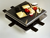 Raclette with vegetables and cheese slices as ingredients