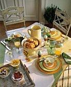 Breakfast table with Easter eggs, breads and pastries etc