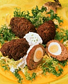 Meatballs stuffed with egg on curly endive with yoghurt sauce