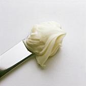 Sahniger Schmelzkäse als Brotaufstrich auf Messer