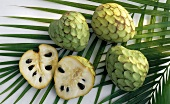 Cherimoya, three whole and one halved, on palm leaf