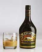 Baileys in bottle and with ice in whisky tumbler