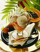Three scoops of walnut ice cream with cream on papayas