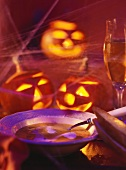 Pumpkin cream soup with sour cream, decor; illuminated pumpkins