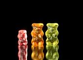 Three gummi bears against black background