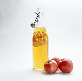 Bottle of apple vinegar and three apples