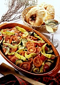Greek vegetables in clay bowl; 2 pita breads in bread basket
