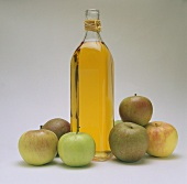 A bottle of cider vinegar, decoration: six fresh apples