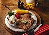 T-bone steak with corncobs, grilled tomatoes & baked potato