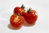Two whole and one half tomato against white background