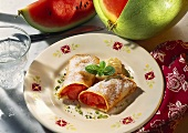 Crepes with melon filling, icing sugar and cream on plate