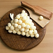 Butter balls on wooden board in shape of bunch of grapes