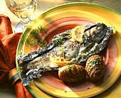Trout, baked in foil, with baked potatoes on plate