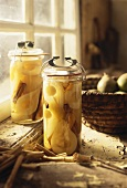 Two jars of bottled pears in front of kitchen window