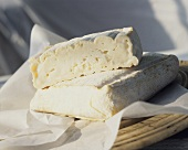 Two pieces of raw milk soft cheese on greaseproof paper