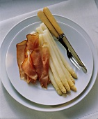 White asparagus with smoked ham on a plate