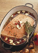 Roast pork with apples and shallots in roasting dish