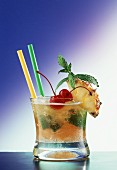 A glass of Mai Tai with straws; limes, pineapple, cherry