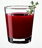 A glass of beetroot juice garnished with thyme sprig