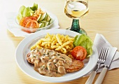 Escalope with mushroom cream sauce, noodles & bowl of lettuce