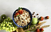 Oat muesli in bowl, fresh fruit & ingredients beside