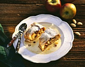 Two pieces of apple strudel with custard on plate