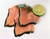 Three slices of Graved Lachs, garnished with dill, lime slice