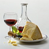 A piece of Parmesan on plate, décor: red wine glass & bottle