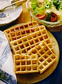 Four cheese waffles (one broken) on wooden board
